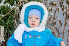 Bébé garçon étonné avec une neige à un jardin d'hiver Image stock