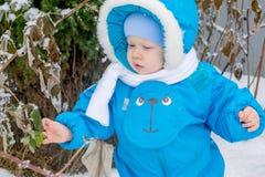 Bébé garçon étonné avec une neige à un jardin d'hiver Photographie stock