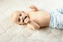 Bébé garçon adorable avec la tétine dans la chambre à coucher ensoleillée blanche Enfant riant mignon image libre de droits