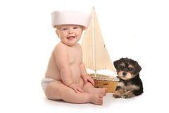Bébé garçon adorable avec son chiot de Yorkie de tasse de thé d'animal familier Image libre de droits