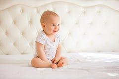 Bébé garçon adorable dans la chambre à coucher ensoleillée blanche Photos libres de droits
