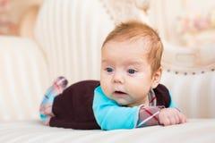 Bébé garçon adorable dans la chambre à coucher ensoleillée Enfant nouveau-né détendant sur le divan Enfant nouveau-né pendant le  Photo libre de droits