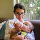 Bébé garçon alimenté par une jolie jeune femme Photographie stock
