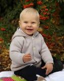 Bébé garçon 1 années, posant avec le potiron et les jouets parmi des arbres i Photographie stock