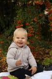 Bébé garçon 1 années, posant avec le potiron et les jouets parmi des arbres i Photos stock