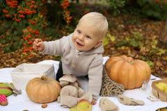 Bébé garçon 1 années, posant avec le potiron et les jouets parmi des arbres i Photo stock