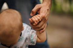 Bébé garçon apprenant à marcher et faisant ses premières étapes tenant des mains de père Image libre de droits