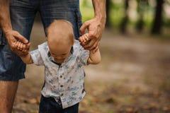 Bébé garçon apprenant à marcher et faisant ses premières étapes tenant des mains de père Photo stock