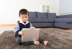 Bébé garçon asiatique à l'aide du comprimé images stock