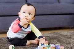 Bébé garçon asiatique avec des doigts dans la bouche au salon images libres de droits