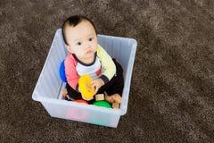 Bébé garçon asiatique jouant à l'intérieur de la boîte en plastique Images libres de droits