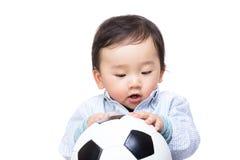 Bébé garçon asiatique regardant le ballon de football photographie stock