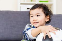 Bébé garçon asiatique tenant le ballon de football Image stock