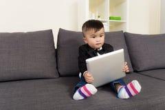Bébé garçon asiatique tenant le comprimé photos stock
