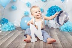 Bébé garçon avec des yeux bleus nu-pieds dans le pantalon avec des bretelles, couvertes caché sous le chapeau, se reposant sur le Photos stock