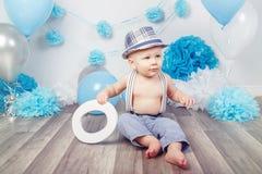 Bébé garçon avec des yeux bleus nu-pieds dans le pantalon avec les bretelles et le chapeau, se reposant sur le plancher en bois d Photo libre de droits