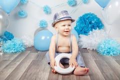 Bébé garçon avec des yeux bleus nu-pieds dans le pantalon avec les bretelles et le chapeau, se reposant sur le plancher en bois d Images libres de droits