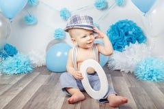 Bébé garçon avec des yeux bleus nu-pieds dans le pantalon avec les bretelles et le chapeau, se reposant sur le plancher en bois d Photos stock