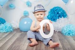 Bébé garçon avec des yeux bleus nu-pieds dans le pantalon avec les bretelles et le chapeau, se reposant sur le plancher en bois d Image stock