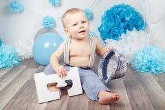 Bébé garçon avec des yeux bleus nu-pieds dans le pantalon avec les bretelles et le chapeau, se reposant sur le plancher en bois d Photographie stock libre de droits