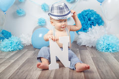 Bébé garçon avec des yeux bleus nu-pieds dans le pantalon avec les bretelles et le chapeau, se reposant sur le plancher en bois d Images stock