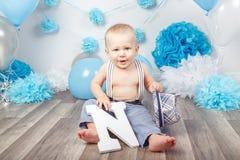 Bébé garçon avec des yeux bleus nu-pieds dans le pantalon avec les bretelles et le chapeau, se reposant sur le plancher en bois d Image libre de droits