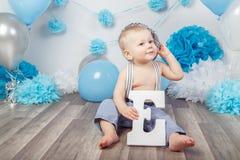 Bébé garçon avec des yeux bleus nu-pieds dans le pantalon avec les bretelles et le chapeau, se reposant sur le plancher en bois d Photographie stock