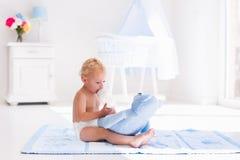 Bébé garçon avec la bouteille à lait dans la crèche ensoleillée Image stock
