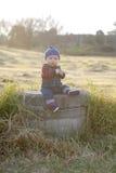 Bébé garçon avec la calotte un jour rougeoyant d'automne image stock