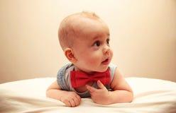 Bébé garçon avec le noeud papillon se trouvant sur le lit Image libre de droits