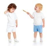 Bébé garçon avec le pinceau et fille tenant intégral d'isolement Photographie stock libre de droits