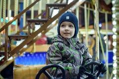 Bébé garçon ayant l'amusement dans un carrousel Photo stock