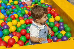 Bébé garçon ayant l'amusement jouant dans une piscine en plastique colorée de boule Photographie stock libre de droits