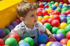 Bébé garçon ayant l'amusement jouant dans une piscine en plastique colorée de boule Image libre de droits