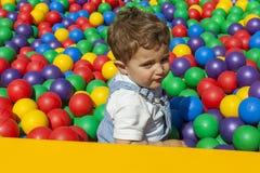 Bébé garçon ayant l'amusement jouant dans une piscine en plastique colorée de boule Images stock