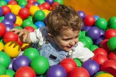 Bébé garçon ayant l'amusement jouant dans une piscine en plastique colorée de boule Photos libres de droits