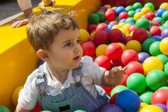 Bébé garçon ayant l'amusement jouant dans une piscine en plastique colorée de boule Image stock