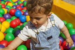 Bébé garçon ayant l'amusement jouant dans une piscine en plastique colorée de boule Photo libre de droits
