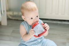 Bébé garçon buvant de la tasse de bébé Photographie stock libre de droits