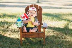Bébé garçon caucasien portant le chapeau canadien et les lunettes drôles de feuille d'érable photographie stock libre de droits