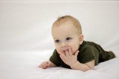 Bébé garçon concentré sur le lit Photographie stock libre de droits