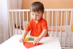 Bébé garçon construisant la maison avec des détails de papier Photographie stock libre de droits