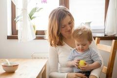 Bébé garçon dans des mains de sa mère mangeant une pomme Photo libre de droits