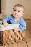 Bébé garçon dans des vêtements sport se reposant à l'intérieur de la boîte tressée à la maison Image libre de droits