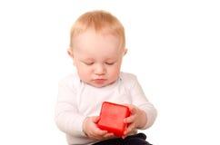 Bébé garçon dans jouer blanc avec le bloc rouge de jouet Images stock