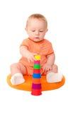 Bébé garçon dans jouer orange avec la tour de jouet Image libre de droits