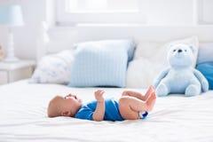 Bébé garçon dans la chambre à coucher ensoleillée blanche Images libres de droits