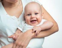 Bébé garçon dans le confort des bras de mamans Photo stock