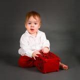 Bébé garçon dans une chemise blanche et des jeux rouges de pantalon image stock