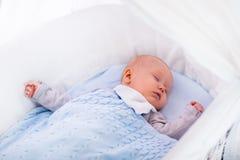 Bébé garçon dans une huche sous la couverture tricotée Photographie stock libre de droits